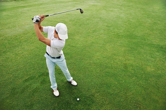 High overhead angle view of golfer hitting golf ball on fairway green grass
